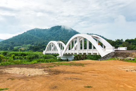 old white railway bridge and mountain in background with overcast sky lamphun thailand Stock Photo