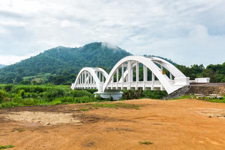 oude witte spoorbrug en de bergen op de achtergrond met bewolkte hemel Lamphun thailand Stockfoto