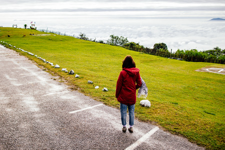 woman wear red coat looking fog and misty on mountain in sunrise time