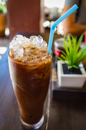 ice coffee with milk on topping drinking in glass on table