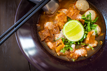 Thai Noodles spicy tom yum soup with pork and lemon on topping street food in thailand Stock Photo