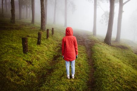 vrouw dragen rode jas weer terug kijken op pad manier met mist en mistig in rainingday Stockfoto