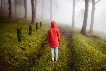woman wear red coat  turn back looking on path way with fog and misty in rainingday