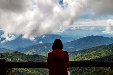 looking at view: traveler woman standing looking view of mountain with cloudy in sky