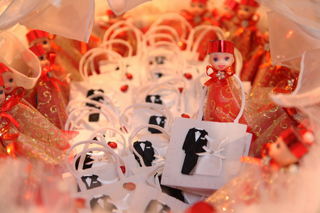 fancy sweet box: Wedding candies. The little cute gifts which the bride and the groom will give to the guests. They have red, yellow and white colors. The background is blurred and the bokeh seems.