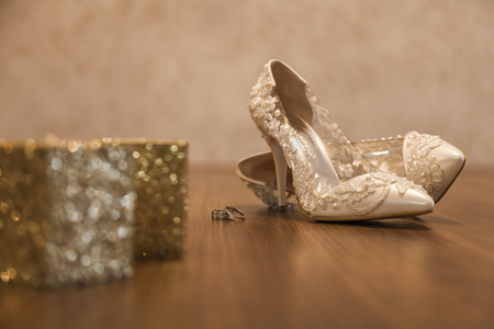 gril: Bridal shoes and rings. Bridal shoes look stylish and beautiful. Photo with warm tones and close-ups.
