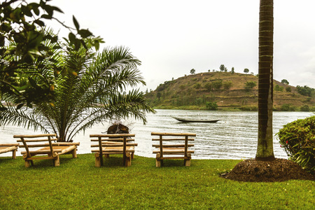湖と島の景色の間で横に木製のサンベッド。彼らはヤシの木が素敵なビューを作成します。