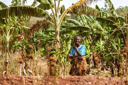Kibuye, Ruanda, Africa - 11 settembre 2015: la donna non identificata. La donna tra alberi di banane in cerca di ridere sembra felice.