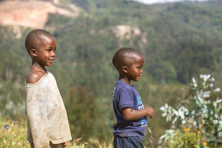 vestidos antiguos: Ruhengeri, Ruanda, África - 9 septiembre 2015: Los niños no identificados. Dos niños pobres con ropa vieja que ven el cielo en el pueblo de montaña en las selvas tropicales. Sonríen y ver el cielo. Editorial