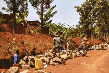 despite: Kibuye, Rwanda - September 11, 2015: Unidentified workers. The workers working on the edges of the road are doing their jobs despite the sun at the top.