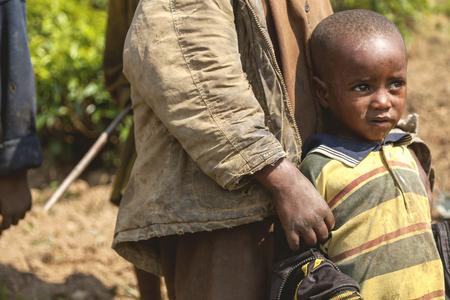 legs around: Ruhengeri, Rwanda - September 9, 2015: Unidentified children. The little boy feared the strangers around leans his back on his brother�s legs.