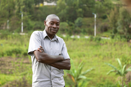 folding arms: Kigali, Rwanda, Africa - September 6, 2015: Unidentified man. The man folding his arms smiles and looks into camera. The man who is behind tea plantations seems happy. Editorial