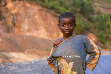 dejected: Kigali, Rwanda, Africa - September 6, 2015: Unidentified child. An African boy. He puts his hands on his waist and there is a dejected smile on his face. Editorial