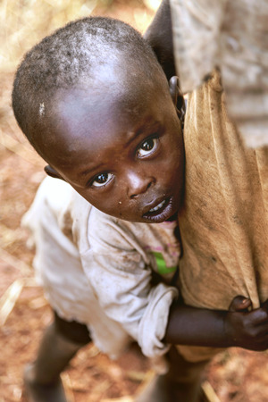 timid: Kibuye, Rwanda, Africa - September 11, 2015:  Unknown children. The little, timid African boy. He clung to his brother's leg and he was looking at the lens with curios and timid eyes.