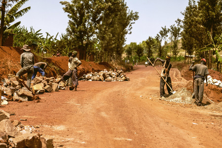 earth road: Kibuye, Rwanda - September 11, 2015:  Unidentified workers. The workers working under the sun. They are fixing the edges of the red earth road.