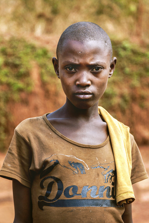 eye traveller: Kibuye, Rwanda, Africa - September 11, 2015:  Unknown girl. The young girl is looking with a face that is angry and nervous. She has short hair and male image and her old clothes reveal her poverty.