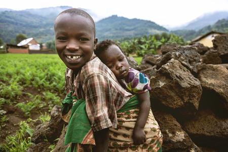 Byumba, Ruanda, Afrika - 6. September 2015: Nicht identifizierte Kinder. Der afrikanische Kind ihren Bruder mit dem Rücken trägt. Das Kind lächelt und scheint sehr glücklich. Editorial