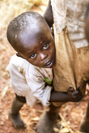 timid: Kibuye, Rwanda, Africa - September 11, 2015:  Unknown children. The little boy who was caught on lens with curious and timid eyes. The little boy with barefoot clung to his brother's leg. Editorial