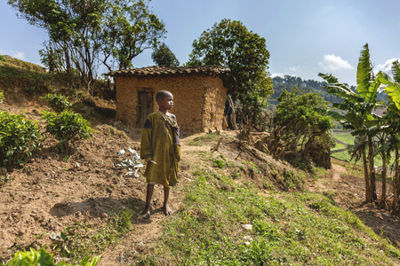Ruhengeri, Rwanda - September 9, 2015: Unidentified African boy. The boy with his clothes being torn and his earthen house watches the sky. He seems happy despite his old clothes.