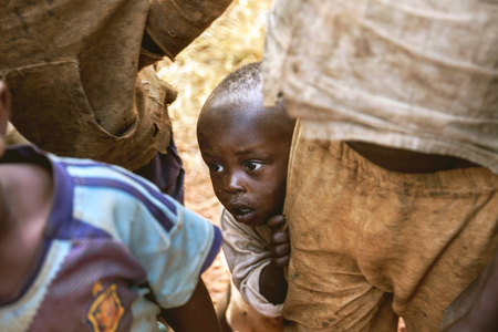 timid: Kibuye, Rwanda, Africa - September 11, 2015:  Unknown children. The little African boy watching the things that happened around with his excited, curious and timid eyes. Editorial
