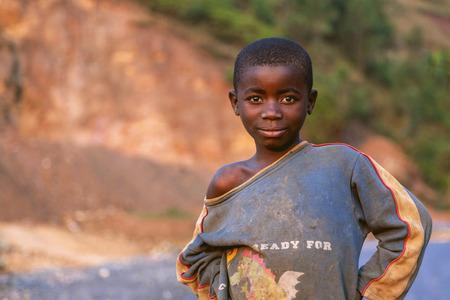 vestidos antiguos: Kigali, Ruanda, África - 6 septiembre 2015: el niño no identificado. El niño africano que sonríe. El chico está en la ropa vieja y uno de sus hombros está fuera. Hay una sonrisa en su rostro abatido.