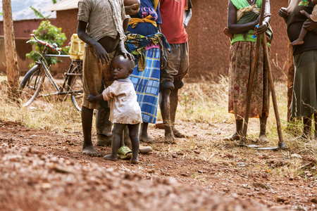 back cloth: Kibuye, Rwanda, Africa - September 11, 2015:   Unknown people. The women with digging tools on her hands is carrying her baby by means of a cloth which is tied with her baby's back.