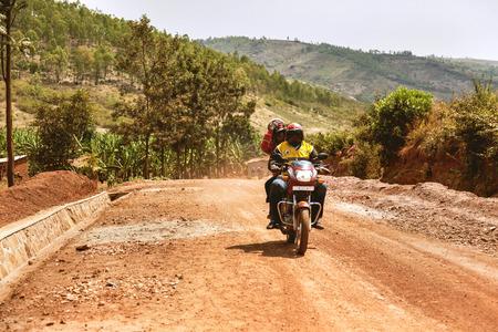 unknown men: Kibuye, Rwanda - September 11, 2015: Unknown men. Two man on motorbike. It goes on red earth road. Editorial