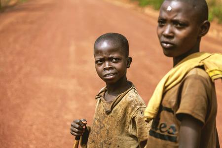 vestidos antiguos: Kibuye, Ruanda, África - 11 de septiembre de 2015: Niños desconocidos. Dos niños pequeños africanos sobre la tierra roja. Su ropa vieja revelan su pobreza, pero los niños no les importa.