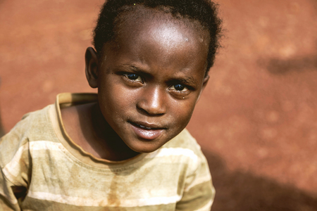 despite: Kibuye, Rwanda, Africa - September 11, 2015: Unknown child. The little African boy. Despite hisher old clothes on him, he is smiling with his eyes being full of hope.