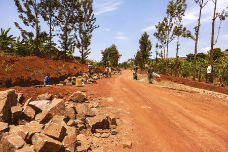 tree works: Kibuye, Rwanda - September 11, 2015: Unidentified the Rwandan workers. The workers working under the sun are with the view of the sky and red land. Editorial