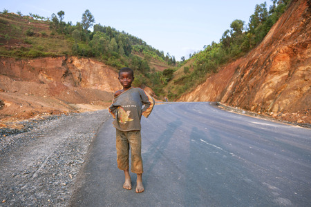 naked child: Kigali, Rwanda, Africa - September 6, 2015: Unidentified child. A child on the asphalt road. The feet of child are naked. Old clothes of the child who smiles show the poverty of him. Editorial
