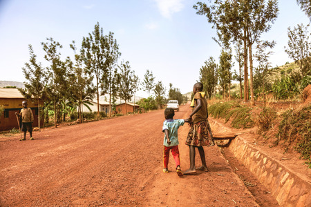 tugging: Kibuye, Rwanda, Africa - September 11, 2015:  Unknown children. The car is going on dirt road and raising a cloud of dust. The African young girl is keeping her brother's arm and tugging at his arm. Editorial