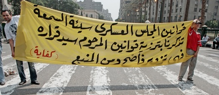 masr: CAIRO - SEPTEMBER 9: Protesters hold signs against the military council in Tahrir square. Cairo, September 9, 2011