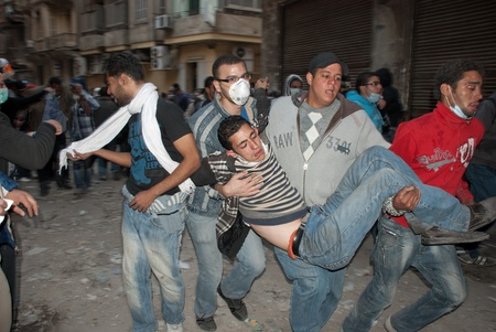 clashes: CAIRO � NOVEMBER 22:  Egyptians carry an injured young man during clashes with police. Cairo, November 22, 2011