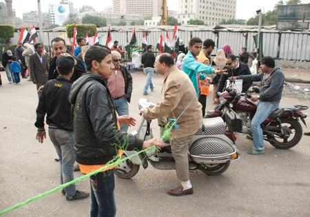CAIRO – NOVEMBER 29: Egyptian young volunteers secure Tahrir Square Entrances to prevent riots in the area during Egyptian parliamentary election, 2011. Cairo, Egypt. November 29, 2011 Editorial