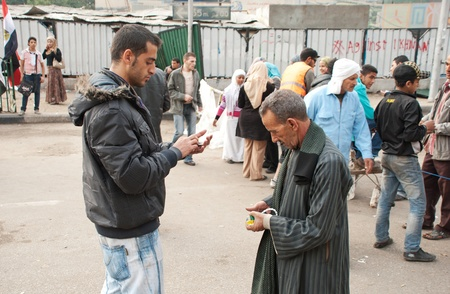 masr: CAIRO � NOVEMBER 29: Egyptian volunteer checking national ID of an old man before going in Tahrir Square during Egyptian parliamentary election, 2011. Cairo, Egypt. November 29, 2011 Editorial