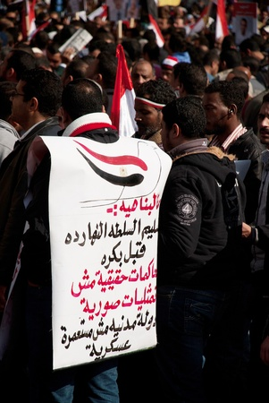 CAIRO – JAN 25: An Egyptian protester wears a big sign against Military council during first anniversary of Egypt
