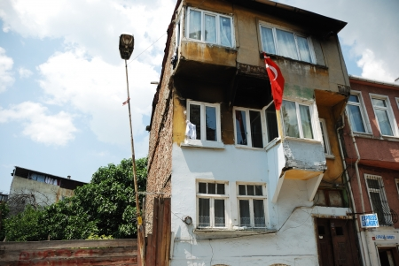fatih: ISTANBUL - MAY 20: An old building in Fatih District with the Turkish flag hanging from a window. Istanbul, Turkey. May 30, 2012