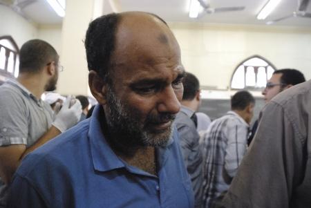malandros: EL CAIRO - 27 de julio: Morsi partidario anciano llora sobre su hijo gravemente herido, mientras que los médicos de hospital improvisado trata de ayudar a la persona a no morir. 27 de julio 2013. El Cairo, Egipto Editorial