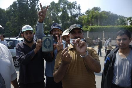 malandros: EL CAIRO - 27 de julio: los partidarios Morsi plantean cartuchos de escopeta disparados por las fuerzas de seguridad y el Sagrado Corán como una manera de apoyar a su moral y que no van a tener miedo de la pistola de la policía. 27 de julio 2013. El Cairo, Egipto