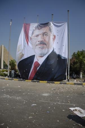 malandros: EL CAIRO - 27 de julio: Gran imagen del derrocado presidente Mohamed Morsi en Rabaa el-adawya donde las fuerzas de seguridad y matones atacaron a los partidarios Morsi. 27 de julio 2013. El Cairo, Egipto Editorial
