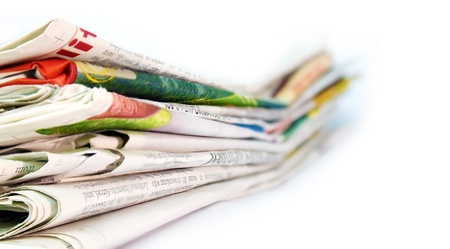 Newspapers stacked against a white background photo