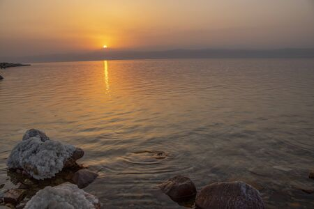sunset at the lowest point in the earth in the dead sea , where located in south of Jordan Фото со стока