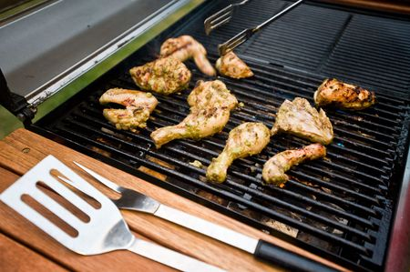 Outdoor BBQ of chicken pieces on hot grill photo