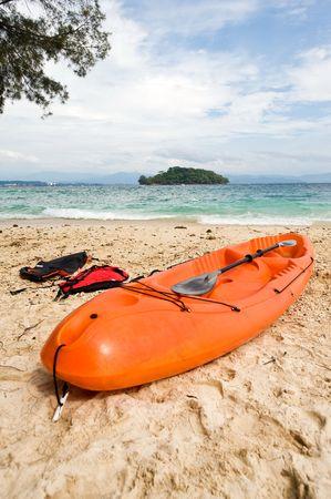 An orange kayak on a beautiful beach ready to be use. photo