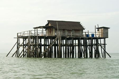 Fisherman house on wooden stilts in the middle of the ocean. photo