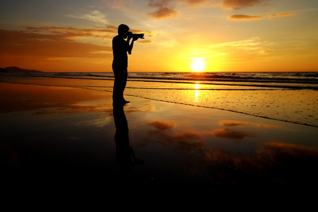 doa: silhouette man take picture on sunset background Stock Photo