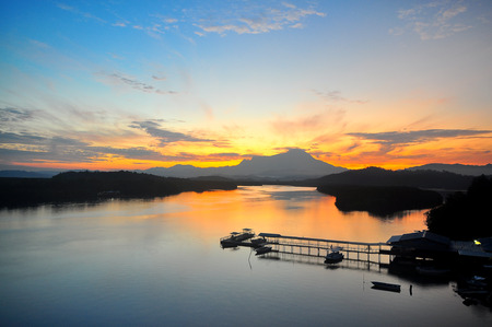 View of Mount Kinabalu in the far horizon seen from the Mengkabong Bridge Sabah Borneo Malaysia. during sunrise. Stock Photo
