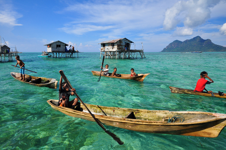 inhabit: SEMPORNA, BORNEO, MALAYSIA - APRIL 18 : Unidentified kids paddle a dug out boat on April 18, 2015 in Semporna, Sabah, Malaysia. They inhabit villages built on stilts in the middle of ocean. Editorial