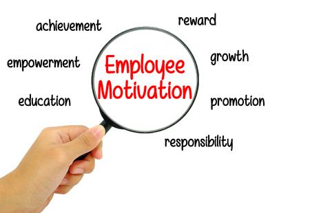 empowerment: Hand holding magnifying glass with Employee Motivation words concept.